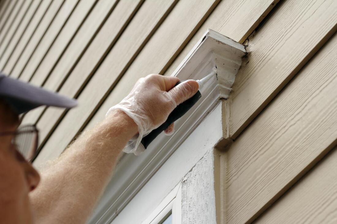 professional painter working on house exterior